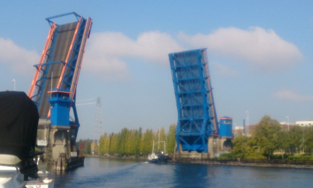 A boat throwing a good-sized wake heading through the Fremont Bridge to saltwater.